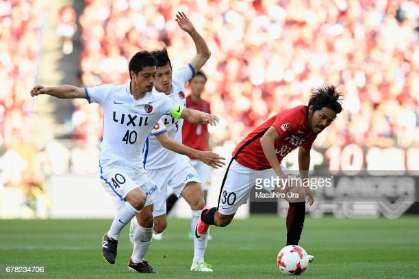 Shinzo Koroki of Urawa Red Diamonds competes for the ball against Mitsuo Ogasawara and Naomichi Ueda of Kashima Antlers during the JLeague J1 match...