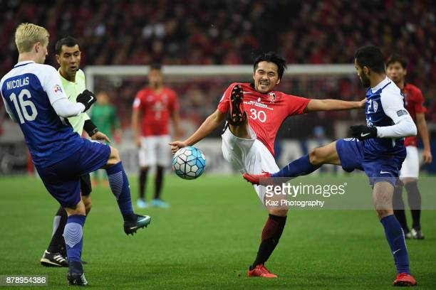 Shinzo Koroki of Urawa Red Diamonds competes for the ball against Mohammed AlBurayk and Nicolas Milesi of AlHilal during the AFC Champions League...