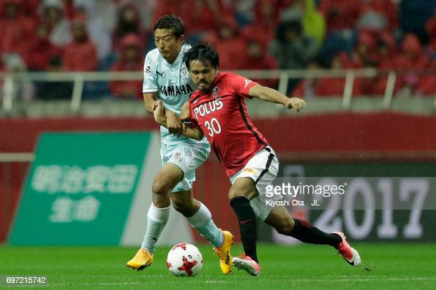 Shinzo Koroki of Urawa Red Diamonds controls the ball under pressure of Kentaro Oi of Jubilo Iwata during the JLeague J1 match between Urawa Red...