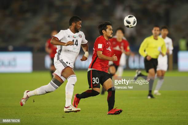 Shinzo Koroki of Urawa Red Diamonds is challenged by Fares Juma of AlJazira during the FIFA Club World Cup match between Al Jazira and Urawa Red...