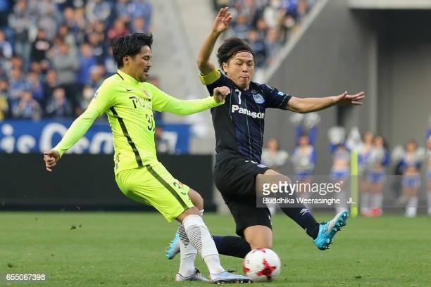 Shinzo Koroki of Urawa Red Diamonds is challenged by Yasuhito Endo of Gamba Osaka during the JLeague J1 match between Gamba Osaka and Urawa Red...