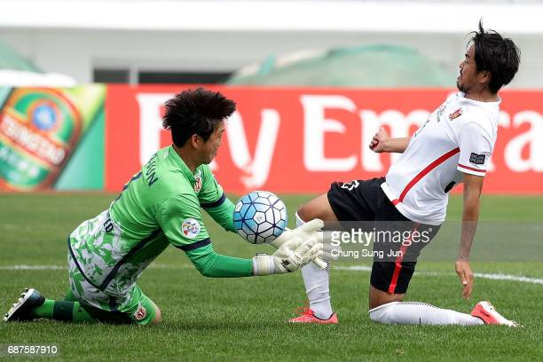 Shinzoh Kohrogi of Urawa Red Diamonds competes for the ball with Kim HoJun of Jeju United FC during the AFC Champions League Round of 16 match...