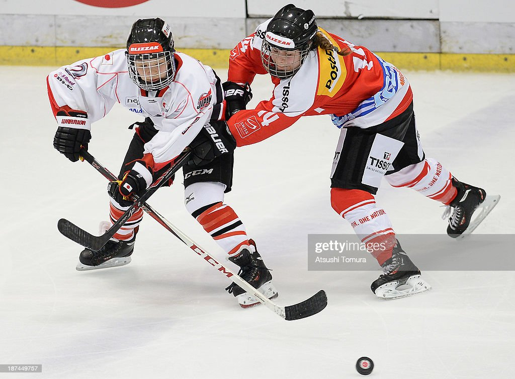 Shiori Koike (L) of Japan and Phoebe Staenz (R) of Switzerland in action in the match between Japan and Switzerland during day three of the Ice Hockey Women's 5 Nations Tournament at the Shin Yokohama Skate Center on November 9, 2013 in Yokohama, Japan.