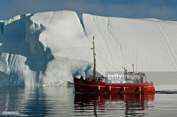 Ship among the icebergs that have broken off the Sermeq Kujalleq ice sheet Ilulissat Qaasuitsup Greenland