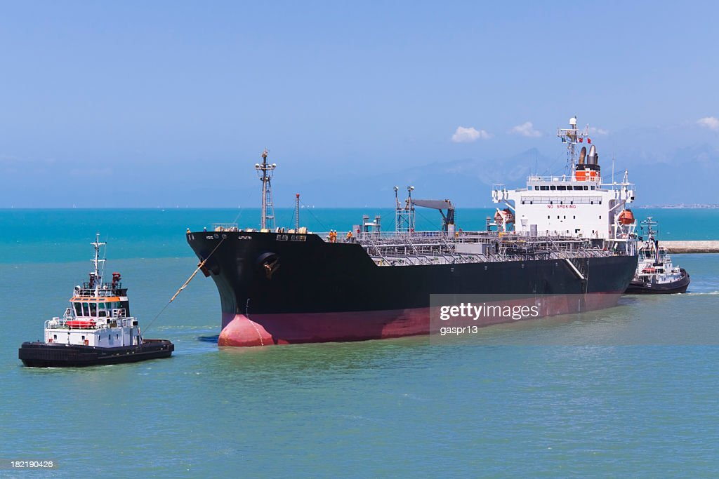 A ship being pulled by a tugboat in the water