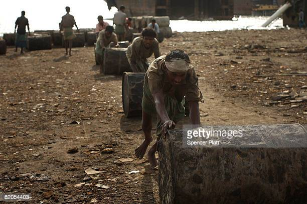 A ship breaker moves a barrel of oil to shore from a ship that is being dismantled for scrap July 24 2008 in the port city of Chittagong Bangladesh...