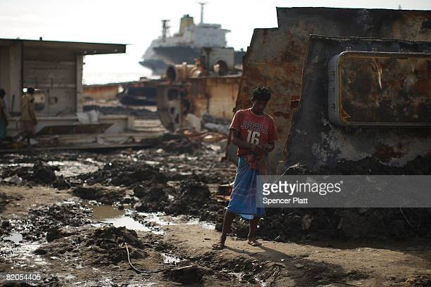 A ship breaker pauses while working on dislodging sheets of metal from a ship that is being dismantled for scrap July 24 2008 in the port city of...