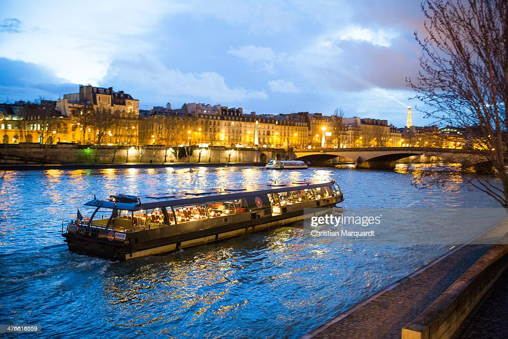 A ship crusing on the Seine during evening time with Eiffel Tower on horizon on February 28, 2014 in Paris, France.