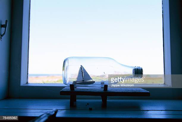 A ship in a bottle in a window.