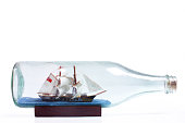 A toy ship in a bottle. The texture of the old glass shows over the miniature ship.