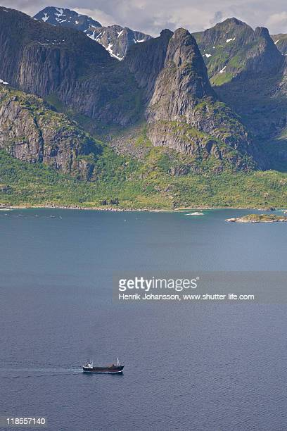 Ship in fjord with high mountains