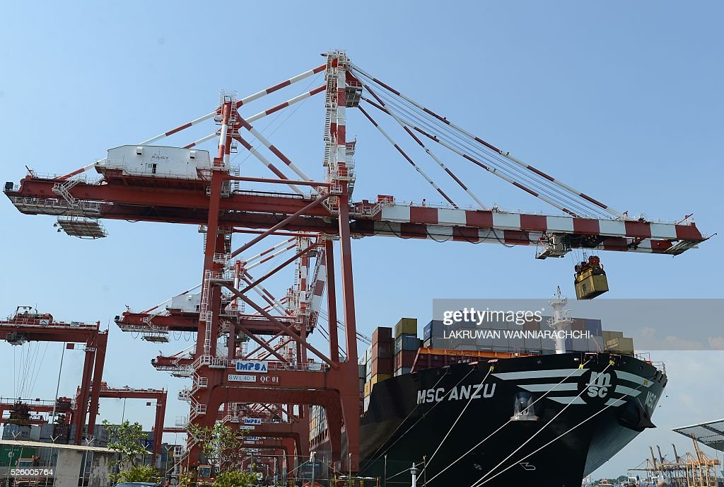 A ship is loaded with containers at the Chinese-majority owned Colombo International Container Terminal (CICT) in Colombo on April 29, 2016. The International Monetary Fund (IMF) has agreed a $1.5 billion loan for Sri Lanka to support economic reforms aimed at reversing a two-decade decline in tax revenue and reviving growth, it said April 29. The International Monetary Fund's chief for Sri Lanka Todd Schneider said a staff-level agreement was reached to release $1.5 billion over a three-year period in support of the island's reform agenda. / AFP / LAKRUWAN