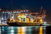 Cargo ship loaded in New York container terminal at night viewed from Elizabeth NJ across Elizabethport reach.