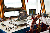 Close view into captain's cabines, navigation equipment and captain's hand on rudder during cruising