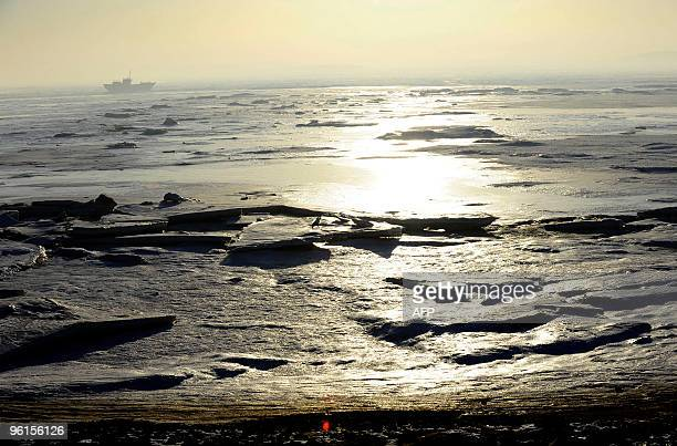 A ship passes on the horizon of the frozen Bohai sea off the coastline in Xingcheng in northeast China's Liaoning province on January 23 2010 A cold...