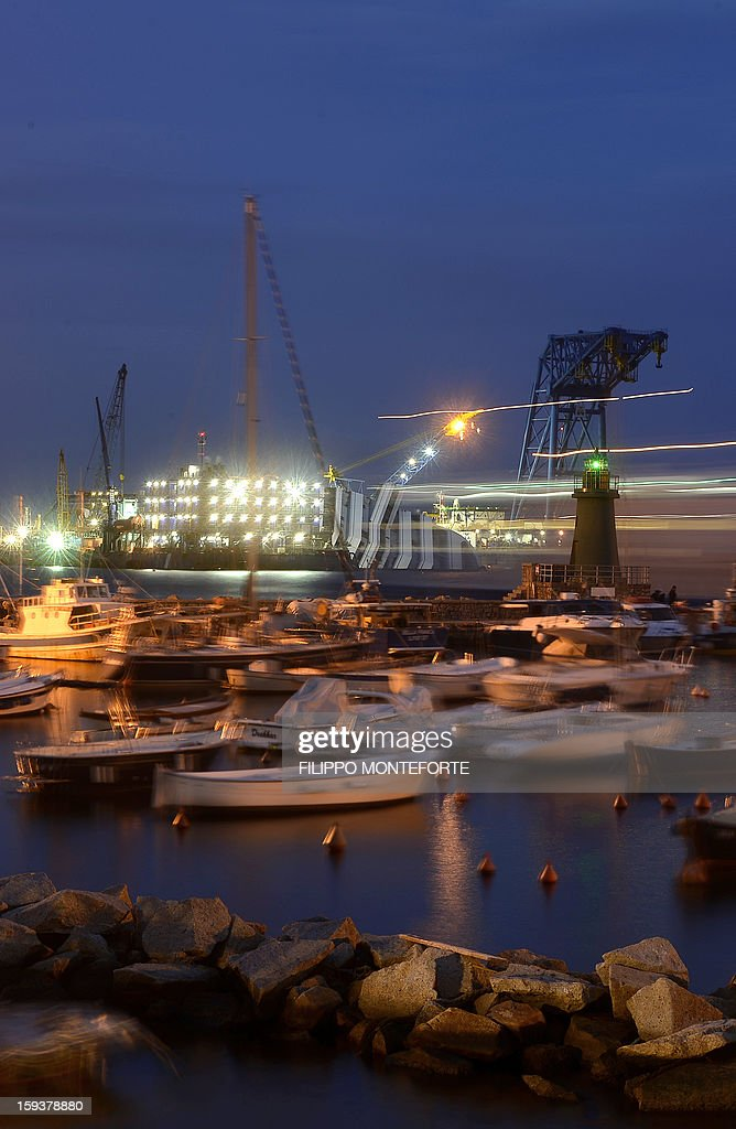 A ship passes the Costa Concordia cruise ship (L) which remains on the shoreline of the Italian island of Giglio on January 12, 2013. Shaken survivors and grieving relatives of the 32 victims of the Costa Concordia cruise ship disaster began arriving on the island of Giglio for a first anniversary commemoration of the tragedy.