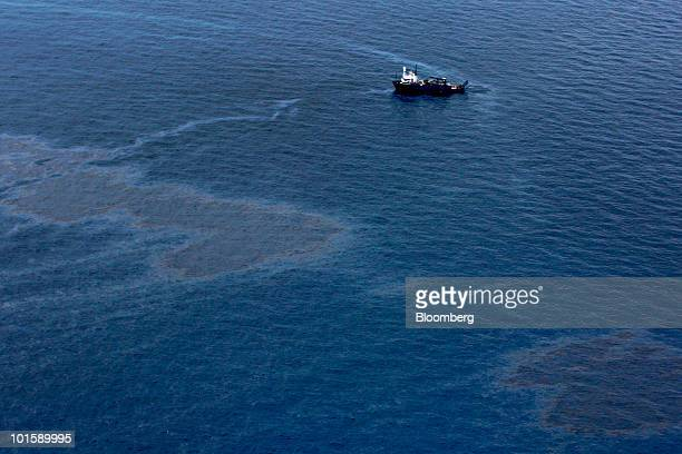 A ship passes through oil floating on the water's surface near the BP Plc Deepwater Horizon oil spill site in the Gulf of Mexico near the coast of...