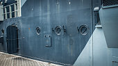 Three portholes looking out onto the deck of an elderly ship.