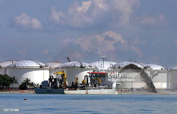 A ship pumps out sand in a reclaimation work next to storage tanks on an Island off Singapore 12 April 2006 Landscarce Singapore will build...