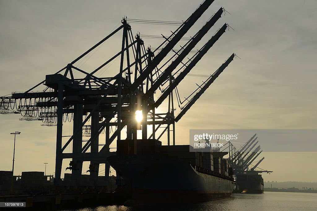 A ship with containers aboard is moored under idle cranes at the Port of Los Angeles in southern California as a strike by port clerical workers enters its second week, December 4, 2012. A federal mediator has been called in to try to break a strike deadlock which has crippled a key US trade hub for the last week. The strike by clerical workers at the ports of Los Angeles and Long Beach, which handle more than 40 percent of ocean-shipped US imports from Asia, is costing billions to the local and wider US economy. The White House said it was monitoring the standoff closely, and LA Mayor Antonio Villaraigosa announced the two sides had agreed to federal mediation, after he spent the night in negotiations himself. AFP PHOTO / Robyn BECK