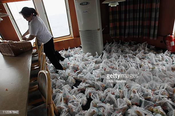 A ship worker on the Ionian Spirit ferry helps bag up over a thousand food bags for evacuees coming on board April 17 2011 in the port in Misrata...