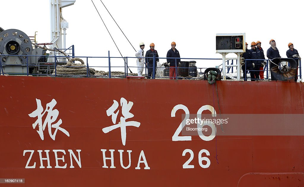 Ship workers stand aboard the Zhen Hua 26, a semi-submersible heavy load carrier operated by Shanghai Zhenhua Heavy Industry Co. Ltd. (ZPMC), as it delivers ship-to-shore container cranes to the new DP World Ltd. London Gateway shipping terminal in Stanford-le-Hope, U.K., on Friday, March 1, 2013. DP World, which operates more than 60 terminals in six continents, said it is on track to open new capacity in Santos in Brazil, Jebel Ali in the United Arab Emirates and London Gateway in the U.K. this year. Photographer: Chris Ratcliffe/Bloomberg via Getty Images