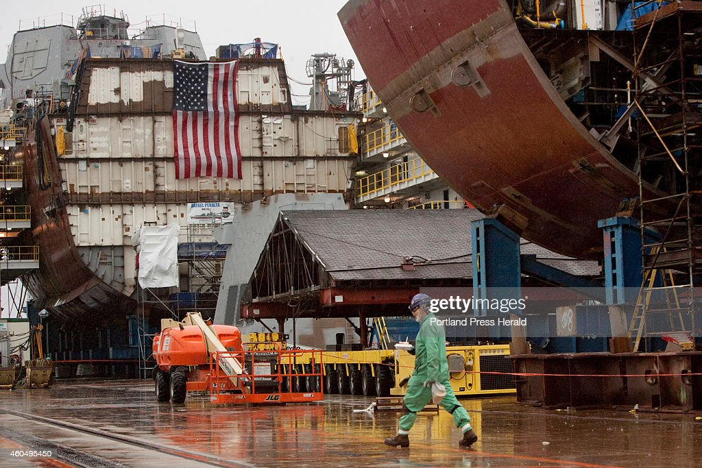 A shipbuilder walks in the yard with partial ship assemblies behind him at Bath Iron Works in Bath on Wednesday December 10 2014