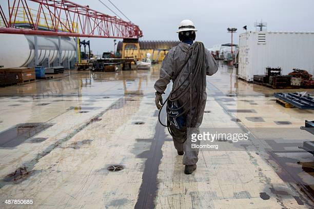 A shipbuilder walks on the deck of the USS Gerald R Ford aircraft carrier during outfitting and testing at Huntington Ingalls Industries' Newport...