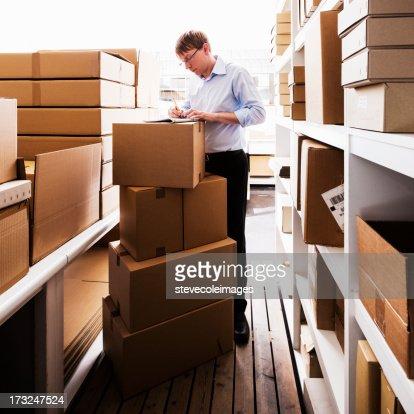 Mann Umgang mit Papierkram in einer Lagerhalle