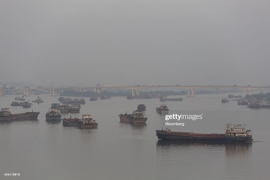 Shipping boats are seen through haze on the Pearl River in Guangzhou, Guangdong province, China, on Tuesday, Nov. 26, 2013. China is proposing the largest package of economic reforms since the 1990s to stoke growth in the worlds biggest emerging market. Photographer: Brent Lewin/Bloomberg via Getty Images