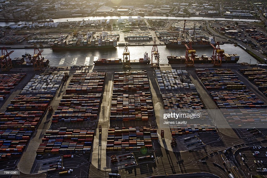 Shipping Container Storage Yard With Ships Loading In Background, Sunset,  Aerial View : Stock