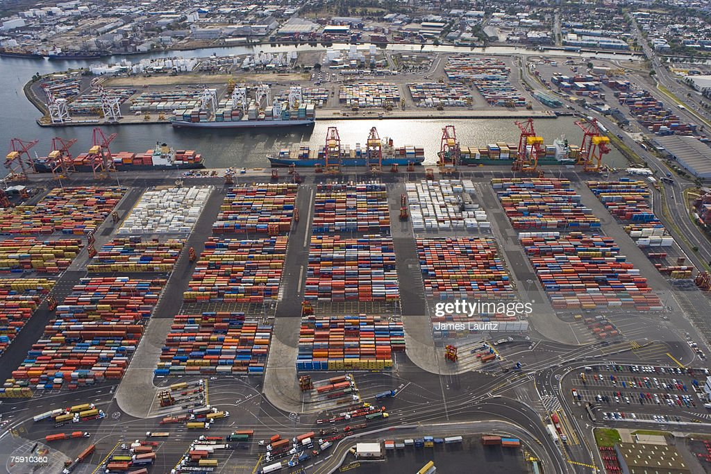 Shipping Container Storage Yard Part - 25: Shipping Container Storage Yards With Trucks In Foreground And Ships  Loading Background, Aerial View :