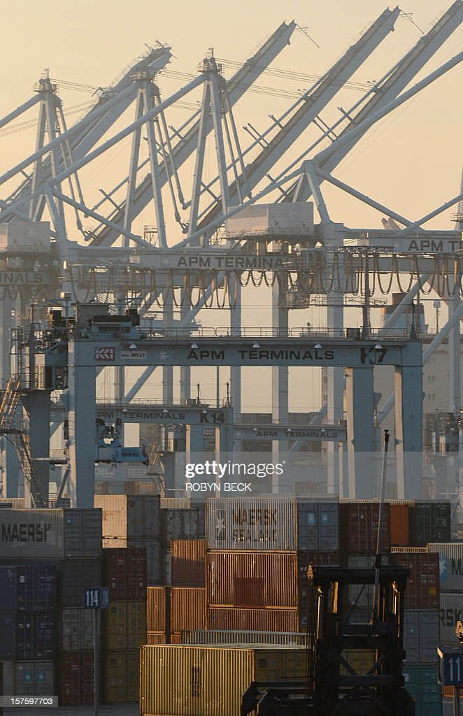 Shipping containers are stack beside idle cranes December 4, 2012 at the Port of Los Angeles in southern California as a strike by port clerical workers enters its second week. A federal mediator has been called in to try to break a strike deadlock which has crippled a key US trade hub for the last week. The strike by clerical workers at the ports of Los Angeles and Long Beach, which handle more than 40 percent of ocean-shipped US imports from Asia, is costing billions to the local and wider US economy. The White House said it was monitoring the standoff closely, and LA Mayor Antonio Villaraigosa announced the two sides had agreed to federal mediation, after he spent the night in negotiations himself. AFP PHOTO / Robyn BECK