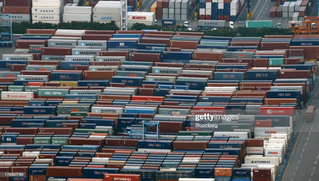 Shipping containers are stacked in Osaka, Japan, on Thursday, Aug. 1, 2013. Prime Minister Shinzo Abe's administration plans to release later this year its medium-term fiscal plans and a final decision on a two-step doubling of the consumption levy to 10 percent in 2015. Photographer: Tomohiro Ohsumi/Bloomberg via Getty Images