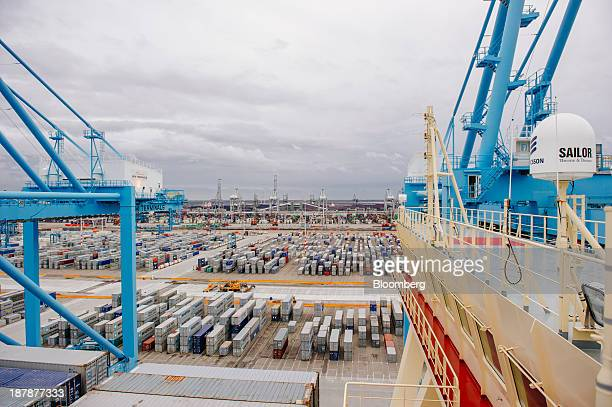Shipping containers sit on the dockside beneath gantry cranes at the Port of Rotterdam seen from the Maersk McKinney Moeller TripleE Class ship...