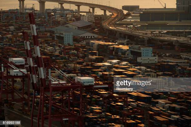 Shipping containers sit stacked among gantry cranes at a container terminal in the Port of Busan in Busan South Korea on Sunday July 16 2017 South...