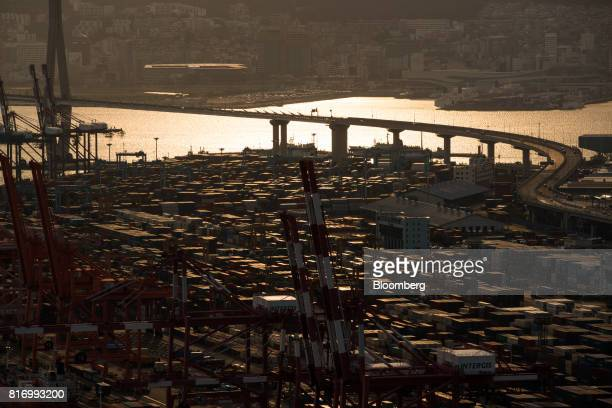 Shipping containers sit stacked among gantry cranes at the Busan Port Terminal at sunset in Busan South Korea on Sunday July 16 2017 South Korea's...
