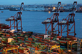 Shipping containers sit stacked next to gantry cranes on the dockside at a shipping terminal at dusk in Tokyo Japan on Tuesday April 21 2015 US and...