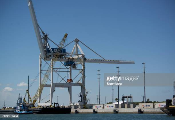 Shipping containers sit stacked under gantry cranes at Port Canaveral in Cape Canaveral Florida US on Wednesday July 5 2017 The US Census Bureau...