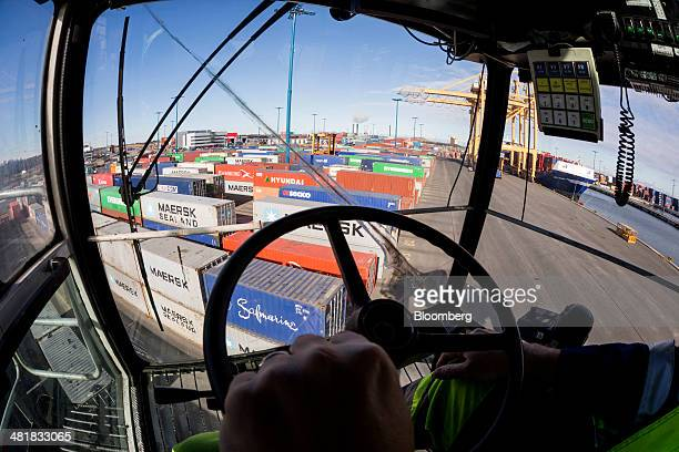 Shipping containers stand on the dockside seen from the control cabin of a straddle container carrier at the Port of Helsinki in Helsinki Finland on...