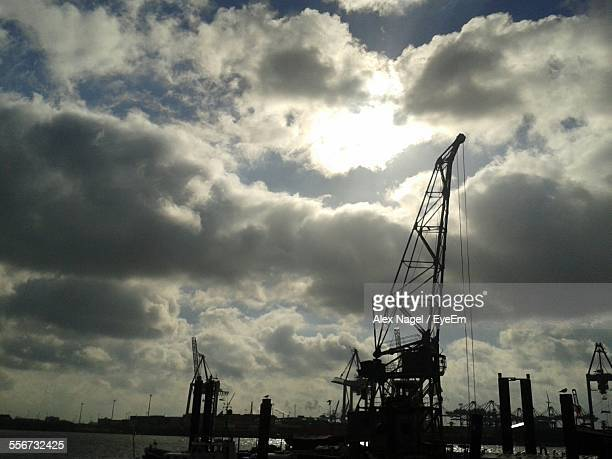 Shipping Cranes Against Cloudy Sky