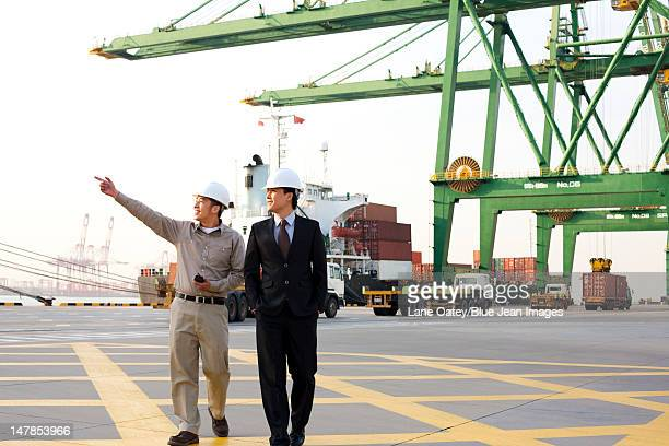 shipping industry worker showing a businessman around the port