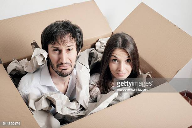 Shipping people in a box - puzzled young couple
