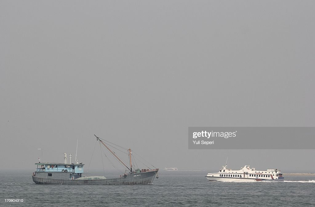 Shipping vessels sail through through haze pollution on the Riau Straits on June 20, 2013 in Bintan Island, Indonesia. The haze, which is created by the illegal burning of forestry in Sumatra in order to make way for palm plantations, is enveloping much of Indonesia, Malaysia and Singapore.