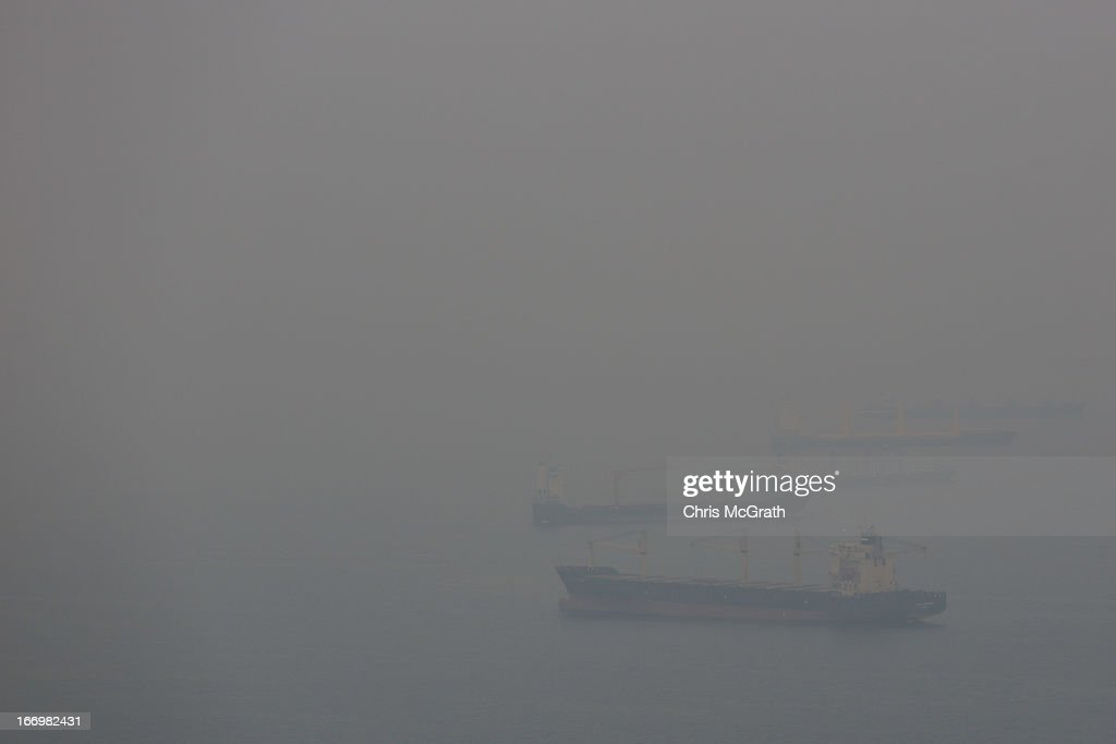 Ships are covered in smoke haze as they wait outside the Singapore port on April 19, 2013 in Singapore. The haze was created by burning off in neighbouring Sumatra and caused the Pollutant Standards Index to rise, hovering between 28 and 43.