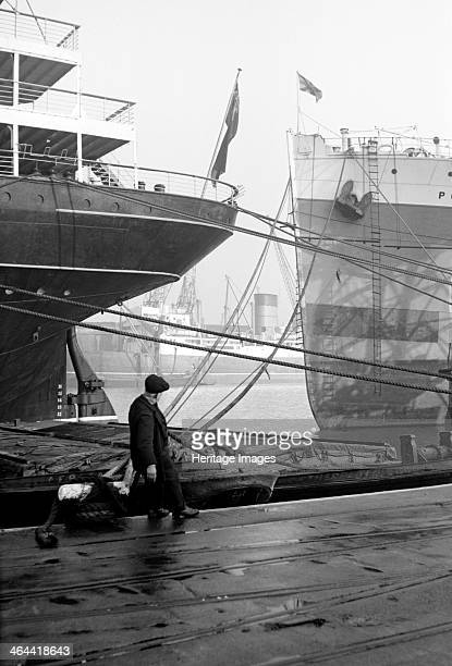Ships berthed at the Royal Albert Dock Canning Town London c1945c1965 With a man pulling a lighter into the dockside for mooring This dock was built...