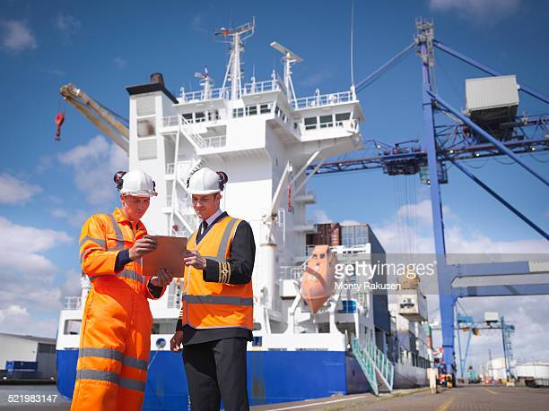 Ships captain discussing loading cargo with port worker