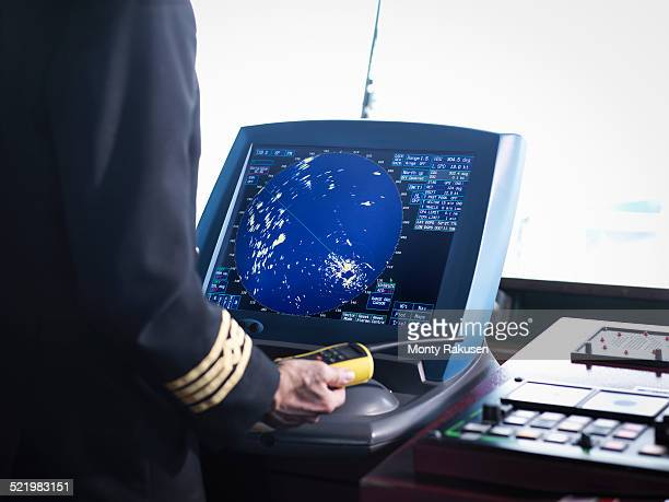 Ships captain working on bridge with radar screen, close up