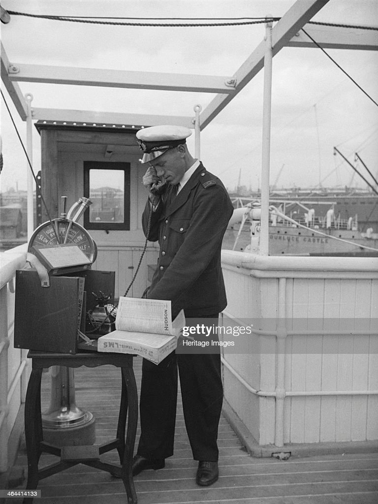 A ship's officer on the bridge uses a portable telephone connected to a land line c1945c1965 His telephone directory is stamped 'Its quicker by rail...