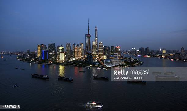 Ships pass by the skyline of the Lujiazui Financial District in Pudong in Shanghai on August 14 2015 AFP PHOTO / JOHANNES EISELE